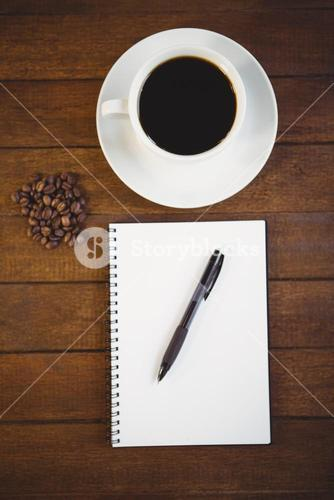 Cup of coffee and notepad with pen