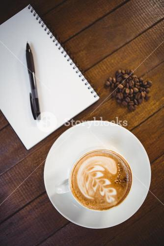 Cup of cappuccino with coffee art and notepad