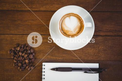 Cup of cappuccino and notepad with pen