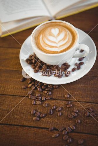 Cup of cappuccino with coffee art and coffee beans