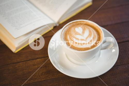 Cup of cappuccino with coffee art next to opened book