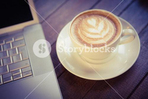 Cup of cappuccino with coffee art next to laptop