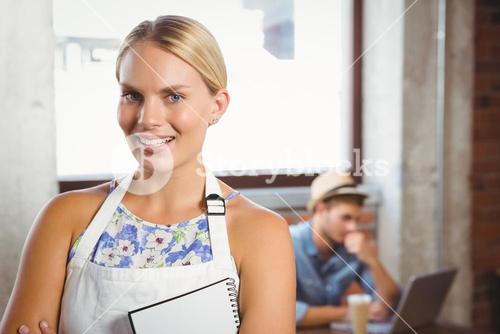 Smiling blonde waitress posing in front of customer