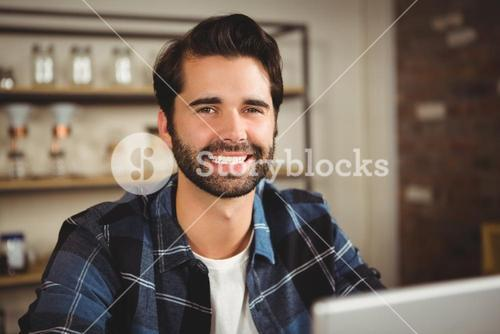 Portrait of a smiling man working on his laptop