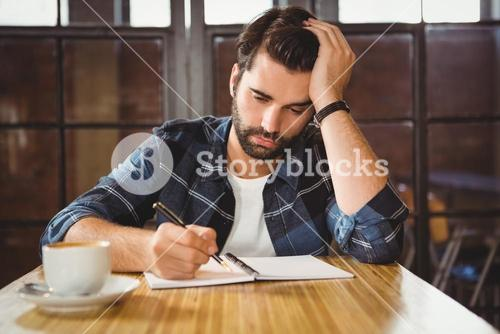 Young man taking notes in his notebook
