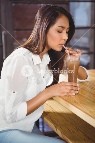 A beautiful woman drinking a hot chocolate
