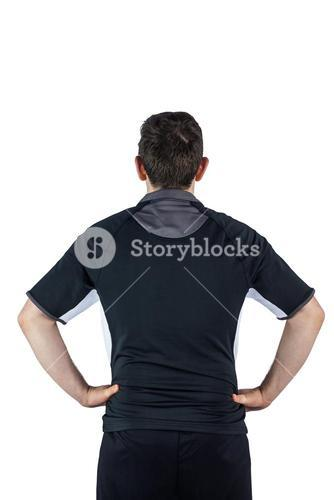Back turned rugby player with hands on hips