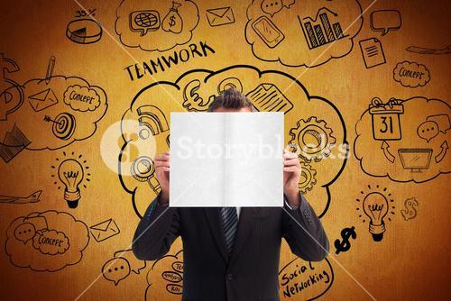 Composite image of businessman holding a white card in front of his face