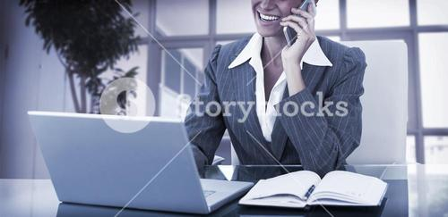Businesswoman on call and using her laptop