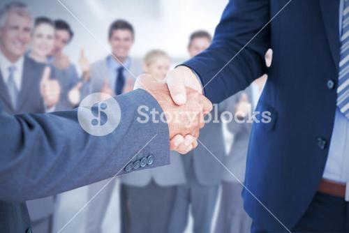 Composite image of businessmen shaking hands