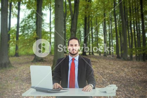 Composite image of unsmiling businessman sitting at desk