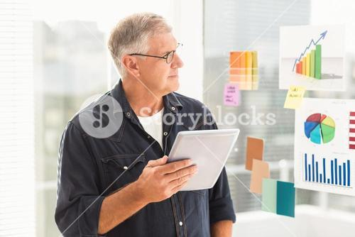 Attentive businessman looking flow charts on the wall