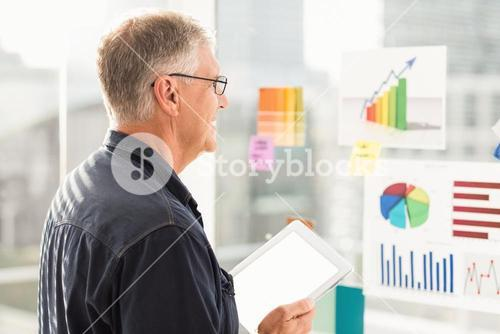 Smiling businessman looking flow charts on the wall