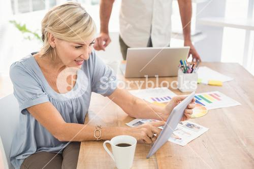 Smiling businesswoman scrolling on a tablet