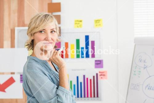 Thoughtful businesswoman writing on a white board
