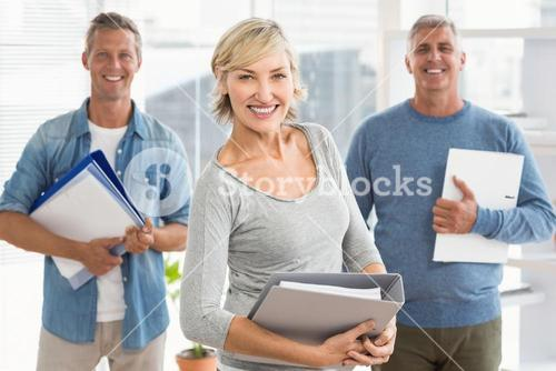 Smiling business colleagues holding workbooks