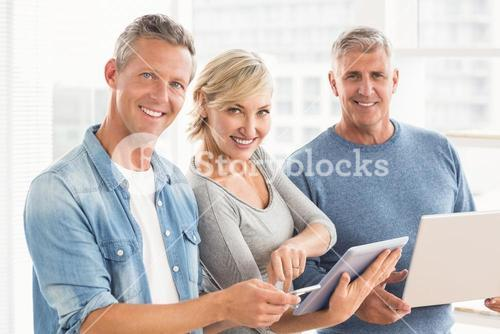 Smiling business colleagues using electronic devices