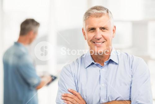 Smiling businessman with arms folded