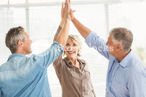 Smiling business colleagues giving high-five