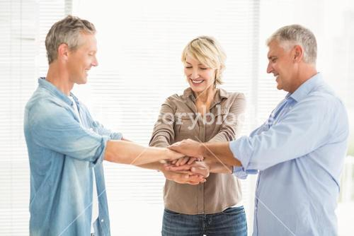 Smiling business colleagues stacking hands