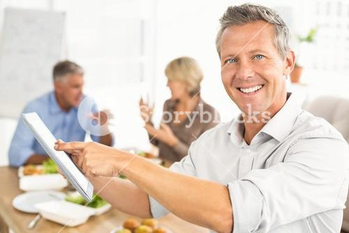 Smiling casual businessman using tablet at lunch