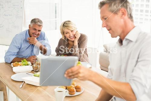 Casual business people looking at tablet while lunch