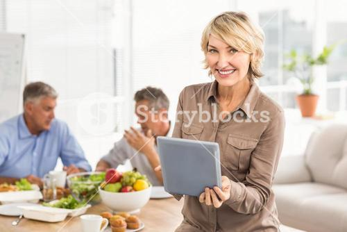 Smiling casual businesswoman using tablet at lunch