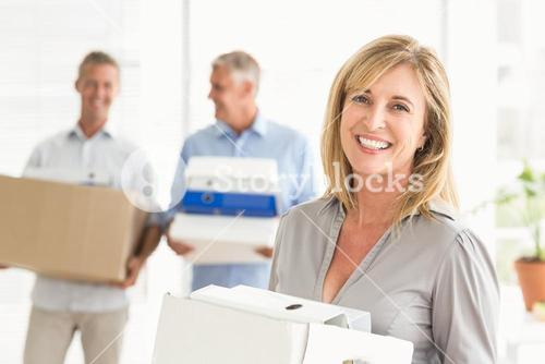 Smiling casual businesswoman with carton