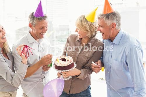 Laughing casual business people celebrating birthday