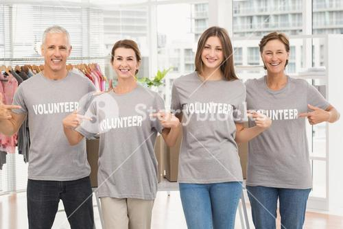 Smiling volunteers pointing on their shirts