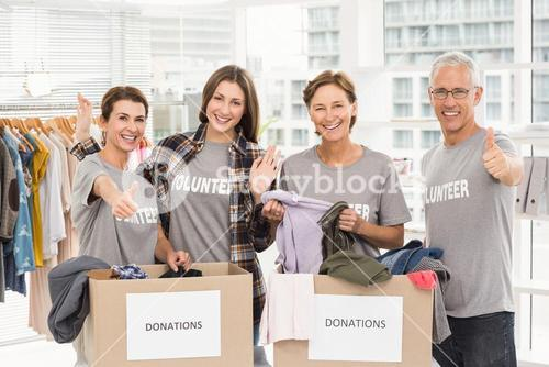 Smiling volunteers with donation boxes
