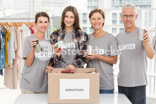 Smiling volunteers showing donations