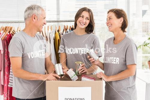 Smiling volunteers sorting donations