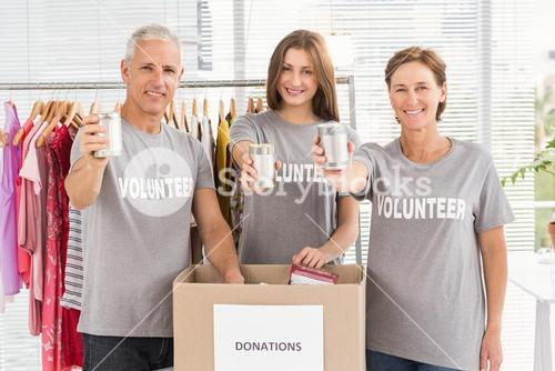 Smiling volunteers showing donated cans