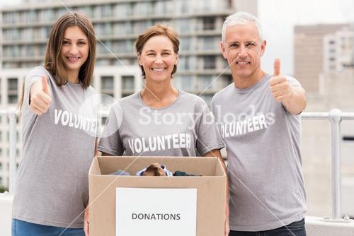 Smiling volunteers with donation box doing thumbs up