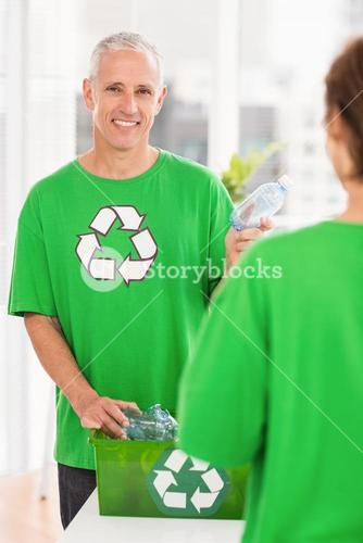 Smiling eco-minded man holding recycling bottle