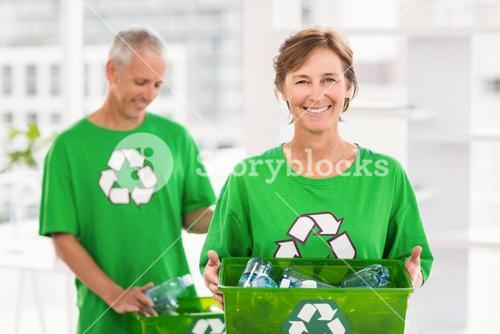Smiling eco-minded woman holding recycling box