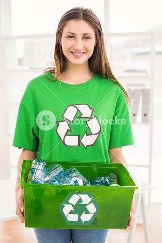 Smiling eco-minded brunette holding recycling box