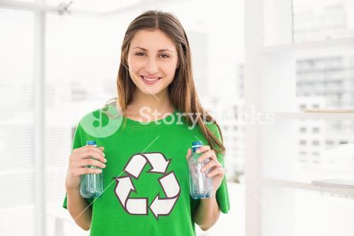 Smiling eco-minded brunette holding recycling bottles