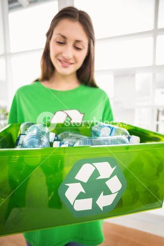 Smiling eco-minded brunette showing recycling box