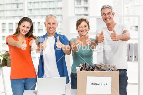 Casual business people donating and doing thumbs up