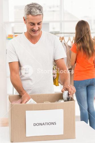 Smiling casual businessman sorting donations