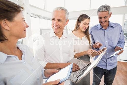 Business people using several electronic devices
