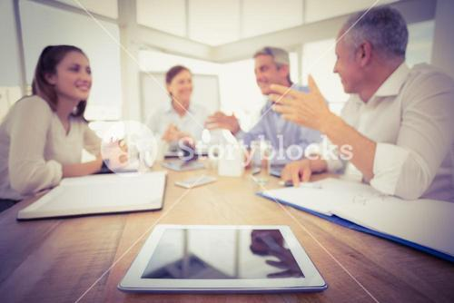 Tablet in front of talking business people