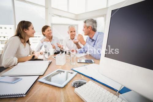 Electronic devices in front of talking business people