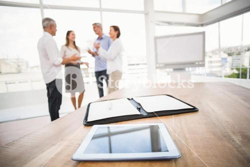 Tablet and planner in front of talking business people