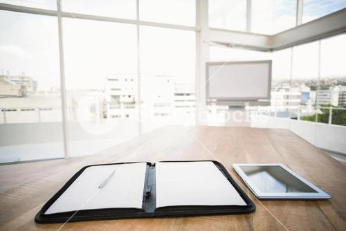 Tablet and planner in front of meeting room