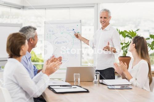 Businessman conducting presentation to colleagues