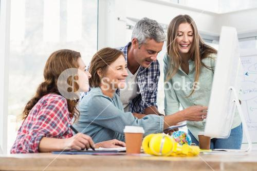 Casual business team having a meeting using a computer