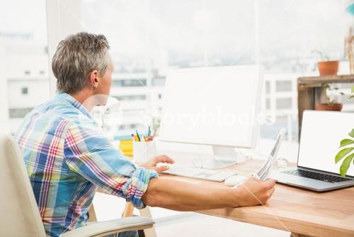 Casual designer editing photos with computer